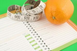 a measuring tape, diet and nutrition journal and an orange